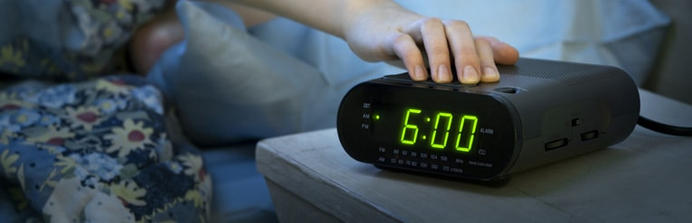 person turning alarm clock off to get up for work